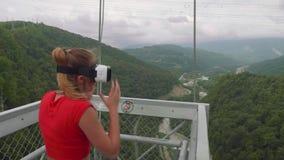Sochi Ryssland - Circa Augusti, 2018: Den unga ilskna blondinen tar bort hennes exponeringsglas 3D mot bakgrund av det gröna berg lager videofilmer
