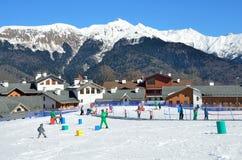 Sochi Ryssland, Februari, 29, 2016, skidar semesterorten Rosa Khutor Undervisningbarn som skidar på, behandla som ett barn skidar Arkivbilder