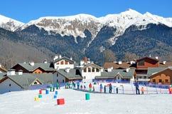 Sochi Ryssland, Februari, 29, 2016, skidar semesterorten Rosa Khutor Undervisningbarn som skidar på, behandla som ett barn skidar Fotografering för Bildbyråer