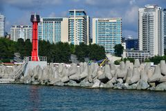 Sochi Ryssland - Juni 2 2018 Röd fyr på vågbrytaren mot bakgrunden av bostads- byggnader arkivbilder