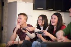 Société de jeunes amis passant le temps ensemble Jeune femme deux jouant le jeu utilisant une manette excitation photos stock