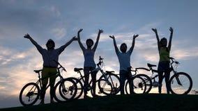 Société de jeunes cyclistes au ciel de coucher du soleil banque de vidéos