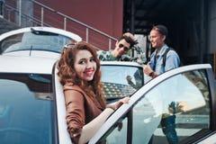 Société de quatre amis entrant dans la voiture Photos stock