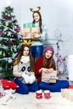 Société de trois filles de chatte près de l'arbre de Noël dans un petit morceau Photo stock