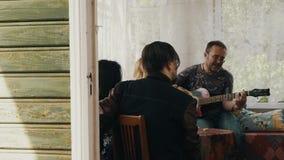 Société des amis à la table sur la terrasse de la maison de campagne La guitare de jeu d'homme chantent clips vidéos