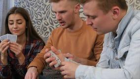 Société des amis s'asseyant à la table à la maison d'étudiant et jouant le jeu de poker Photo libre de droits