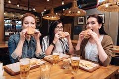 Société des filles avec plaisir goûtant des hamburgers Images stock