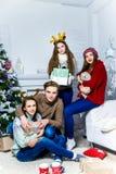 Société du garçon et de trois filles s'asseyant près de l'arbre de Noël Photos stock