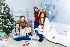 Société du garçon et de trois filles s'asseyant près de l'arbre de Noël Image libre de droits