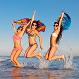 Société gaie des filles sautant en mer Images libres de droits