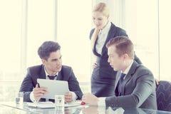 Soci commerciali che discutono i documenti e le idee alla riunione immagine stock