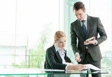 Soci commerciali che discutono i documenti e le idee nell'ufficio Immagine Stock