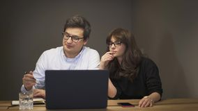 Soci commerciali che hanno una conversazione davanti al computer portatile archivi video