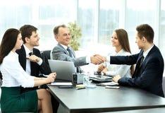 Soci commerciali per discutere piano di cooperazione per il posto di lavoro Immagine Stock