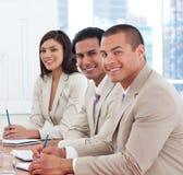 Soci sorridenti di affari in una riunione Fotografie Stock Libere da Diritti