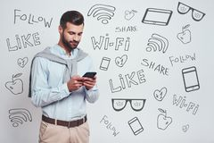 Sociaal media concept Knappe jonge mens in vrijetijdskleding die zijn smartphone met behulp van terwijl status tegen grijze achte stock foto