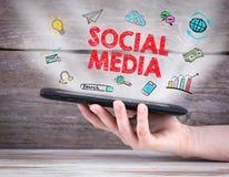 Sociaal media concept tabletcomputer in de hand Oude houten achtergrond stock foto
