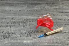 Sociaal probleem Drugs en de maatschappij Gebruikte spuit met staalnaald en lege glasampullen die door rode dunne band worden ver stock foto