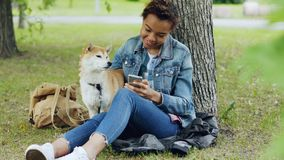 Sociable girl is using smartphone texting friends and stroking her adorable puppy while resting in park at weekend. Sociable girl is using smartphone texting stock video footage