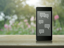 Social chat sign and speech bubbles on modern smart phone screen Stock Image