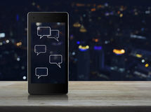 Social chat sign and speech bubbles on modern smart phone screen Stock Photos