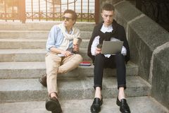 Social communication. Fashion youth outdoors. Two stylish male hipsters on coffee break, creative leisure time, technology concept Royalty Free Stock Photography