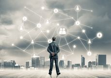 Social connection concept drawn on screen as symbol for teamwork. Back view of businessman looking at modern cityscape and connection concept royalty free stock images