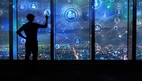 Social Connections with man by large windows at night. Social Connections with man writing on large windows high above a sprawling city at night Stock Photos
