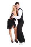 Social dancing. Beautiful blond and brunet dancing salsa on white background Stock Image