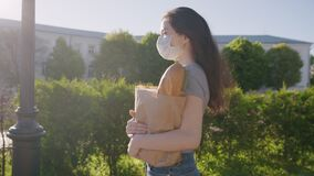 Social distance for prevent outbreak. Pandemic shopping. Young woman in protective mask and gloves carries bag with