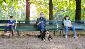 Free Social Distancing: Grandfather And Grandchildren Are Sitting On Park Benches With Masks During The Coronavirus Pandemic Royalty Free Stock Photos - 182578528