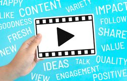 Social entertainment and online marketing concepts with female holding fram of video movie and marketing word on blue color. Background.digital trending ideas stock image