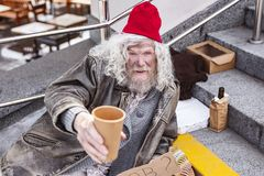 Poor aged man asking for money. Social help. Poor aged man holding a cup while asking for money stock photography