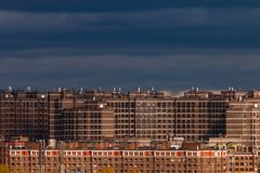 Social housing on the outskirts of the city. Multi-storey residential complex. Construction of a social monotonous dark housing against a dark gloomy sky Stock Photo