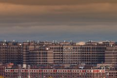 Social housing on the outskirts of the city. Multi-storey residential complex. Construction of a social monotonous dark housing against a dark gloomy sky Stock Photos