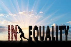 Social inequality concept. Silhouette of a man pushing a word inequality, achieving equality. Social inequality concept stock photo