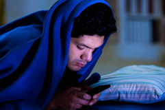 Social media addict men on bed not sleep because play smart phone, covering his head with a blue blanket, room. Social media addict man on bed not sleep because Stock Image
