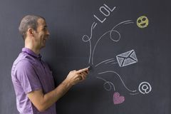 Social media chat with icons and email symbols. Concept of social media chat. Single white adult man standing in front of a blackboard using his smart phone Royalty Free Stock Photo