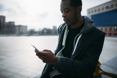 Social media communication. Pensive black man. Chatting on smartphone. Modern lifestyle, street style, young male in selective focus, technology concept Royalty Free Stock Photography