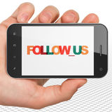 Social media concept: Hand Holding Smartphone with Follow us on  display Stock Image