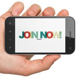 Social media concept: Hand Holding Smartphone with Join now! on  display Royalty Free Stock Image