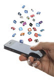 Social media icons fly off the iphone in hand Royalty Free Stock Photo