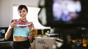 Social media influencer reviewing sports shoe. Smiling young woman vlogging about women`s sports shoe and filming herself at home on a video camera royalty free stock image