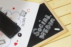 Social Media-Konzept mit Smartphone und Wort SOCIAL MEDIA geschrieben auf Tafel Stockfotografie