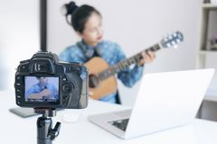 social media learning concept, relaxing and playing guitar, Young woman concentrating learn and play the guitar to a tutorial on