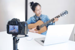Social media learning concept, relaxing and playing guitar, Youn. G woman concentrating learn and play the guitar to a tutorial on lesson online, while she Stock Photography