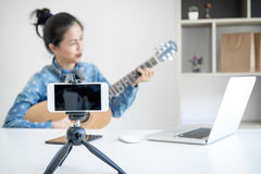 Social media learning concept, relaxing and playing guitar, Youn. G woman concentrating learn and play the guitar to a tutorial on lesson online, while she Stock Images