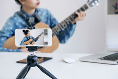 Social media learning concept, relaxing and playing guitar, Youn Royalty Free Stock Photos