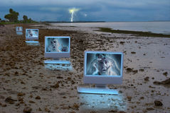 Four computers on a dark stormy beach Stock Photography
