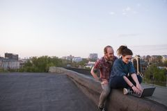 Social media modern youth activity outdoors. Creative couple date on roof, urban background with free space, smiling young people with laptop Royalty Free Stock Photos